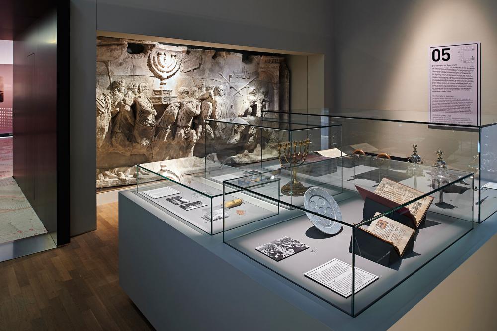 Blick in einen Ausstellungsraum, an dessen hinterer Wand der Gipsabguss des Titusbogens zu sehen ist, im Vordergrund eine Vitrine mit Menora, Tora-Aufsätzen und aufgeschlagenen Büchern