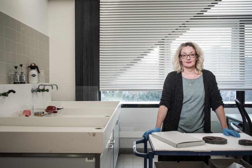 Eine Frau mit blauen Gummihandschuhen steht an einem Arbeitstisch, vor ihr liegen einzelne Objekte.
