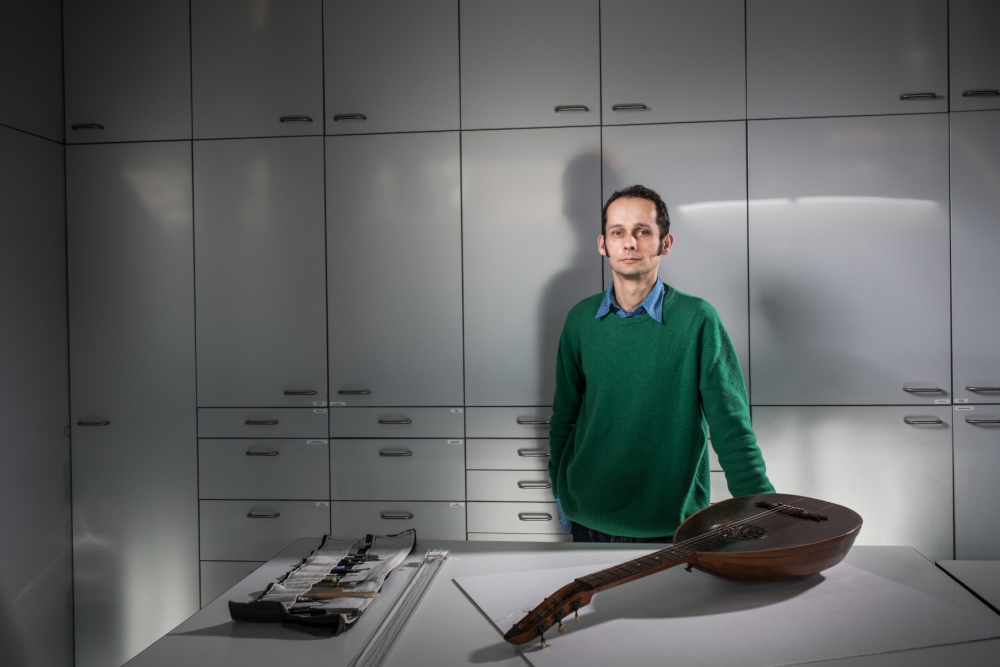 Ein Mann steht hinter einem Arbeitstisch in einem Atelier; vor ihm liegt ein älteres Holzinstrument.