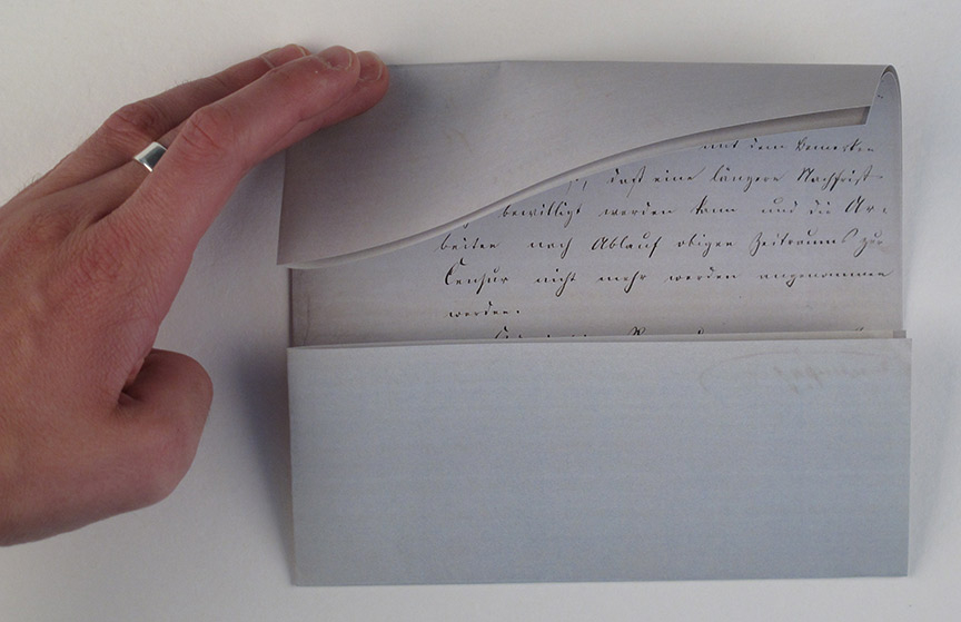 A hand folds a letter