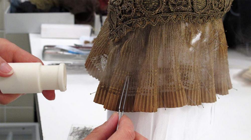 Eine Hand arbeitet mit einer Pinzette an einer Haube