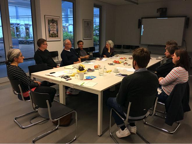 Nine people sit around a table