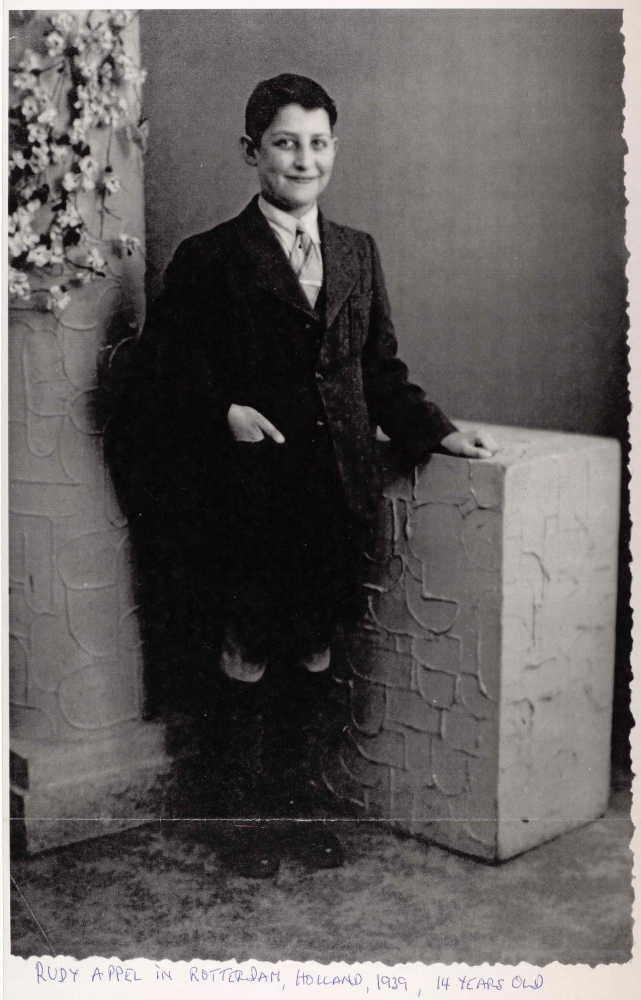Portrait of Rudolf Appel standing in a photo studio. He is wearing a dark suit with short trousers and knee-high socks.
