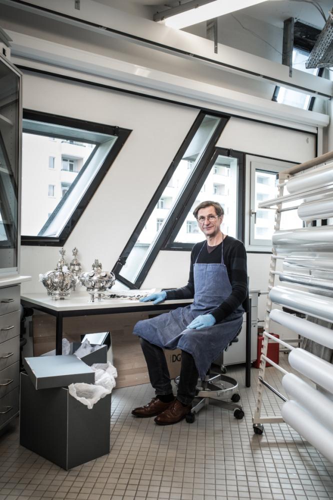 Ein Mann, der in einem Studio am Schreibtisch sitzt, vor ihm stehen metallische Gegenstände.