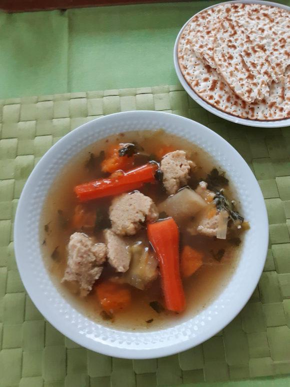 Auf einem grünen Untergrund steht ein Teller mit Hühnersuppe, Karotten und Mazzeklößen. Auf einem weiteren Teller liegt Brot.
