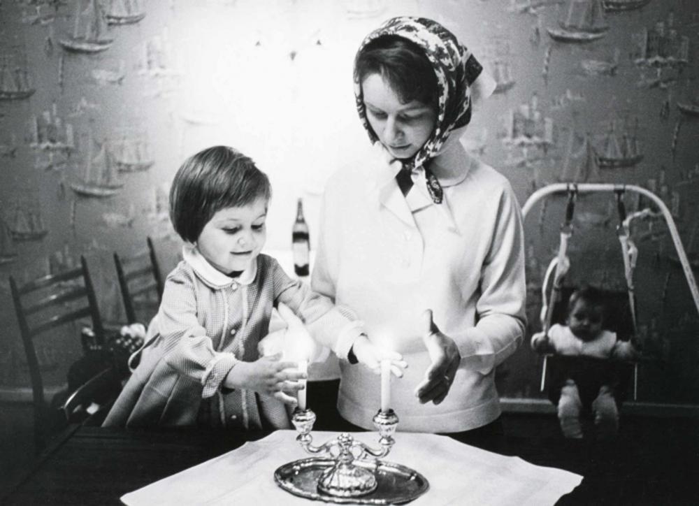Ein kleines Mädchen l. und eine junge Frau mit Kopftuch r. halten ihre Hände neben die Flammen zweier Kerzen, die in einem zweiarmigen Kerzenständer auf einem Tisch mit weißer Tischdecke stehen