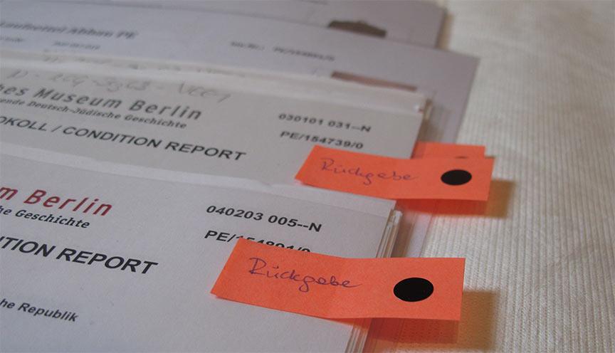 """Stapel mit Protokollen, teilweise mit Klebezettel, auf denen handschriftlich """"Rückgabe"""" steht"""