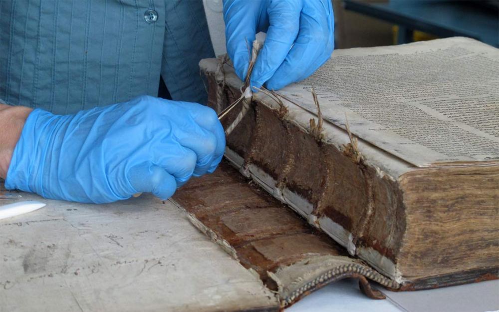 Blau behandschuhte Hände arbeiten mit Pinzette an einem sehr alten, dicken Buch