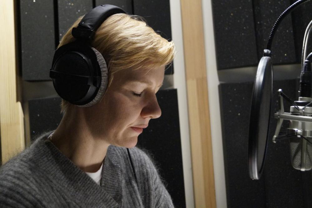 Die Schauspielerin und Sprecherin Sandra Hüller sitzt mit Kopfhörern vor dem Mikrofon im Aufnahmestudio