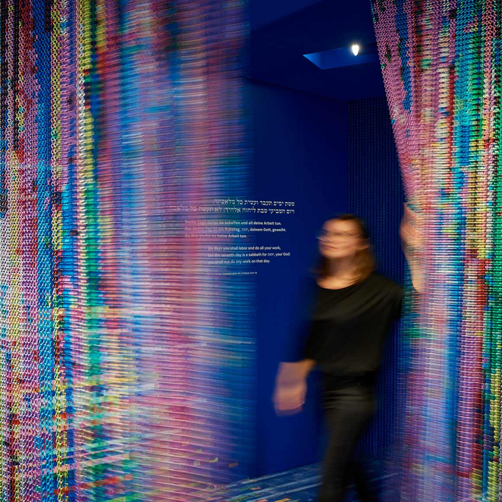A person walks through a colourful glittering curtain, on the wall the commandment to rest on the seventh day (in Hebrew, German and English)