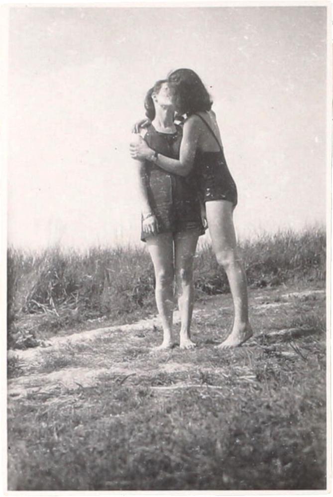 Schwarz-Wieß-Fotografie zweier Frauen im Badeanzug, die sich küssen