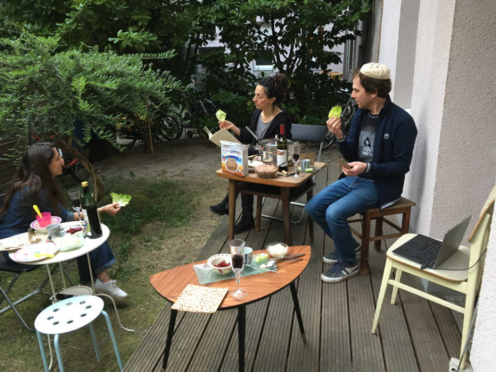 Auf einer Terrasse sitzen drei Menschen mit Abstand zueinander und essen.