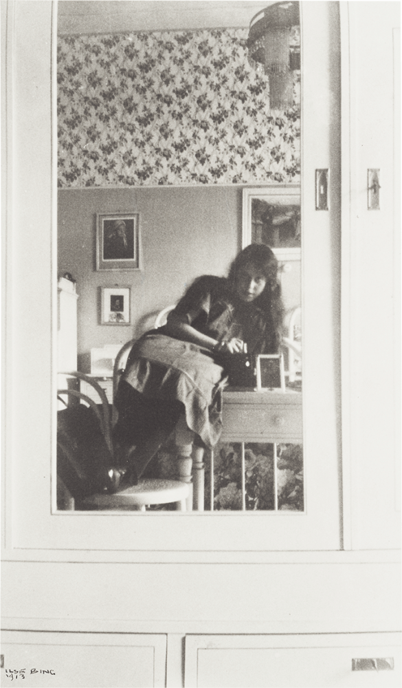 Jugendliches Mädchen in einem Spiegel, der an der Tür eines hellen Schranks befestigt ist