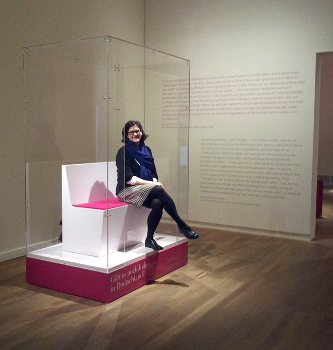 A woman sitting on a bench in a vitreous showcase open at the front