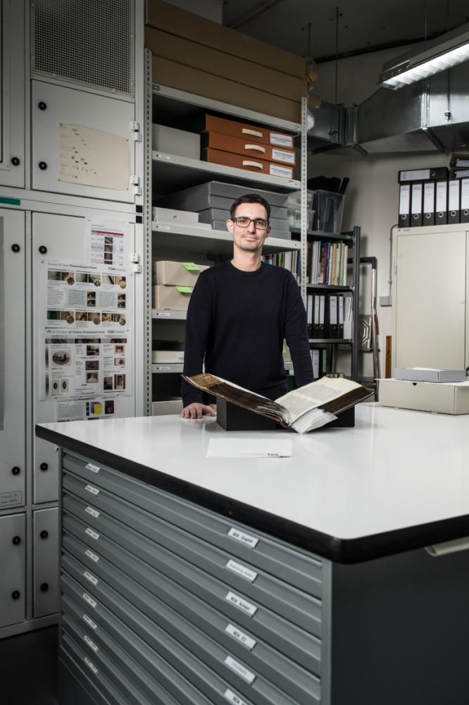 Ein Mann steht hinter einem Arbeitstisch in einem Atelier; vor ihm liegt ein altes aufgeschlagenes Buch