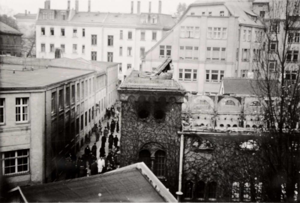 Das Fotot zeigt eine zerstörte Synagoge, deren Dach fehlt, es scheint verbrannt zu sein, Trümmer liegen auf dem noch bestehenden Eingangsportal, in der Staße davor befinden sich viele Passanten.