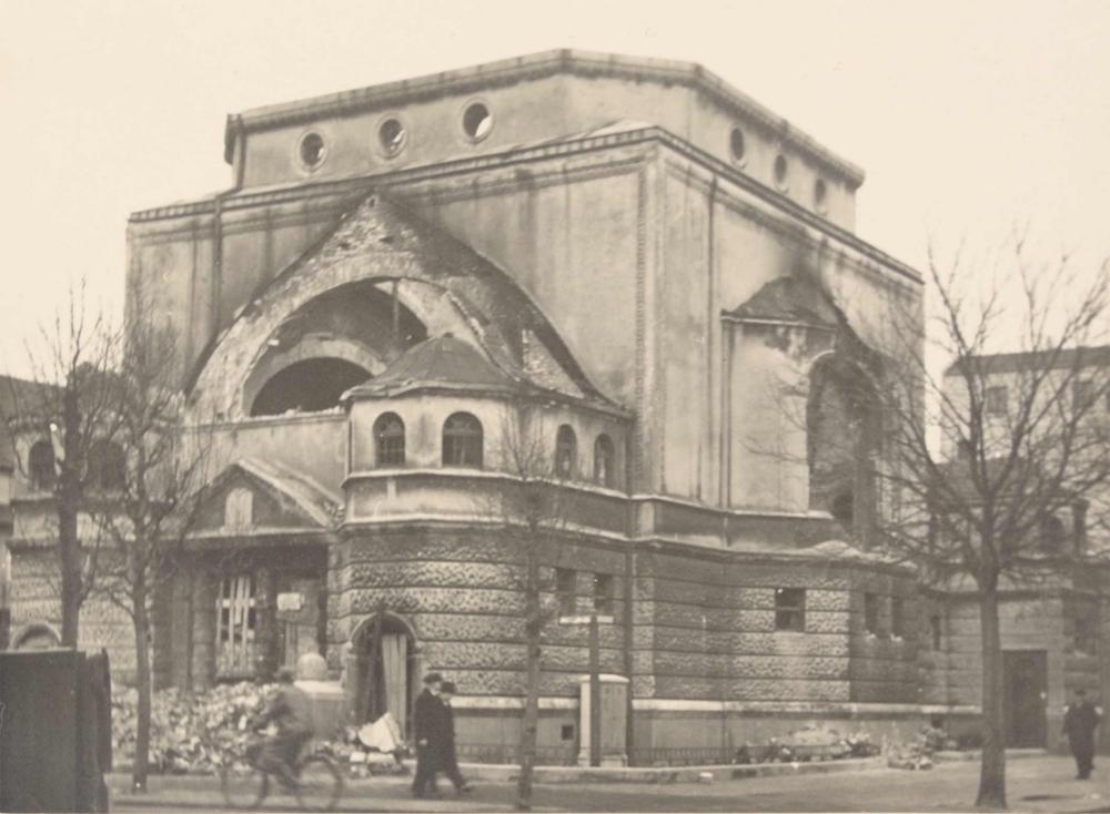 Blick auf die Gebäudeecke der ausgebrannten Synagoge, vor dem Gebäude sind kahle Bäume und Passanten erkennbar.