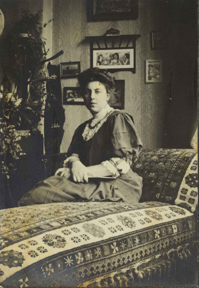 Schwarz-Weiß-Foto einer jungen Frau. Sie sitzt auf einem Diwan mit orientalisch anmutendem Muster und blickt in die Kamera.