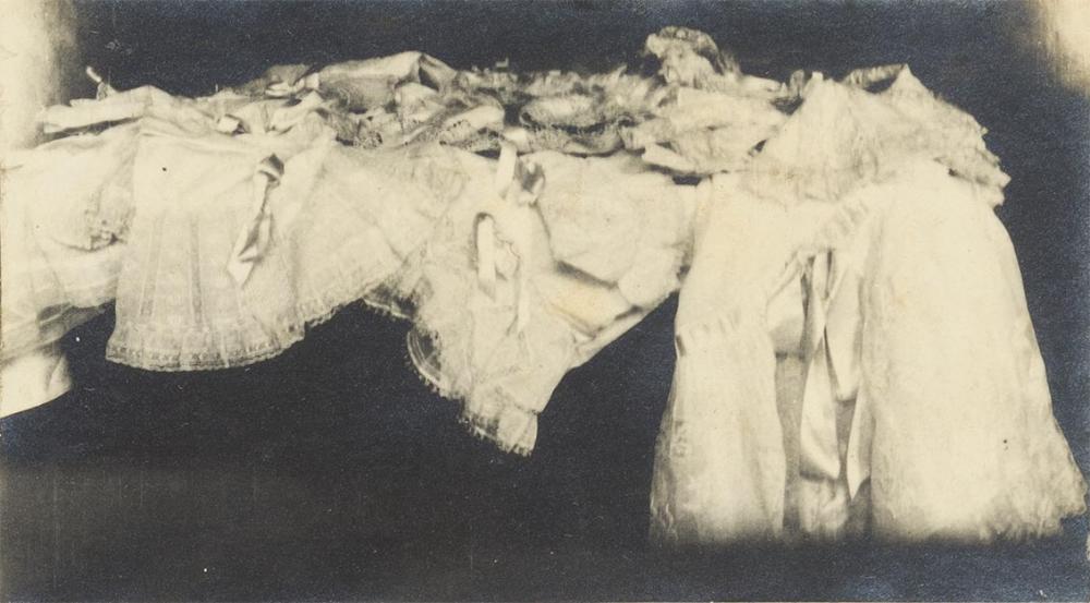 Das Foto zeigt mehrere achtlos abgelegte weiße Unterröcke aus Spitze mit Bändern vor dunklem Hintergrund.