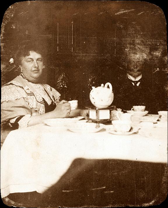 Stark verwittertes Schwarz-Weiß-Foto: Es zeigt ein Paar mittleren Alters, das an einer zum Mittagskaffee gedeckten Tafel sitzt. Beide blicken Richtung Kamera.