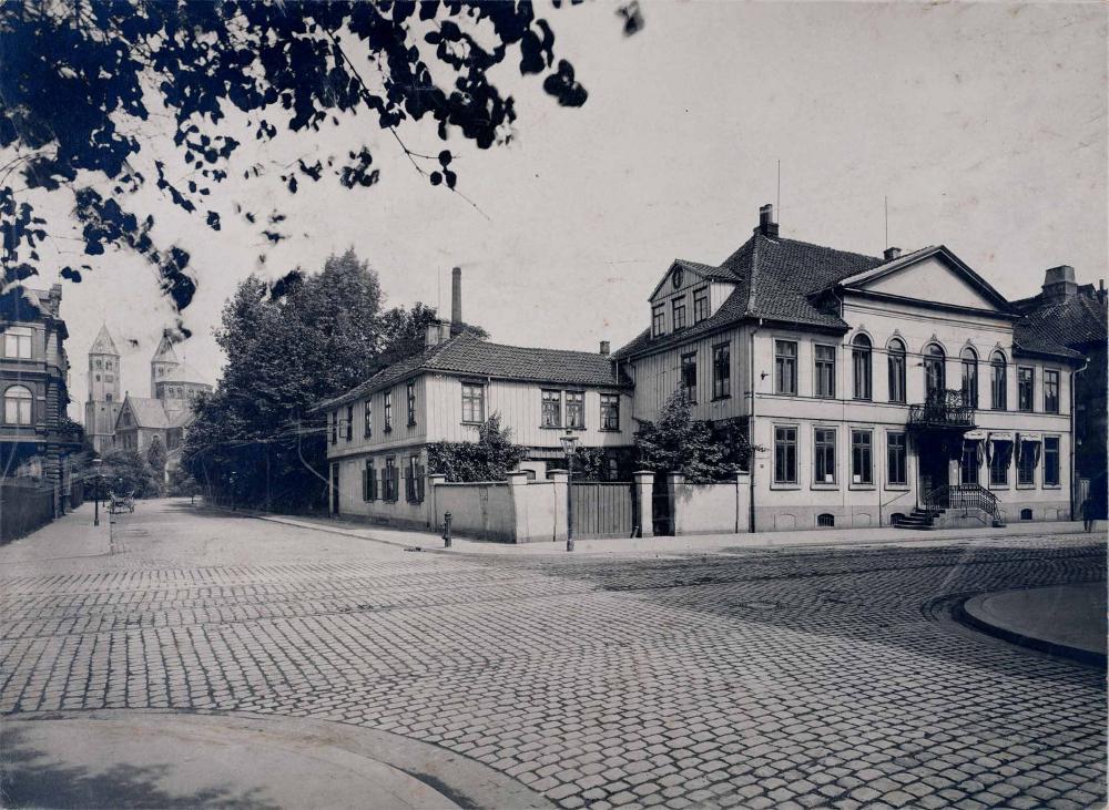 Schwarz-Weiß-Foto eines herrschaftlichen Anwesens auf einem Eckgrundstück.