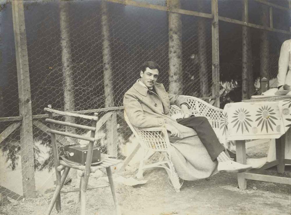 Ein junger Mann mit Schnurrbart im Mantel sitzt an einem Tisch und schaut mit herausforderndem Blick in die Kamera. Vor ihm steht ein Tisch mit Tischdecke, hinter ihm ist ein hoher Zaun aus Hasendraht zu sehen.