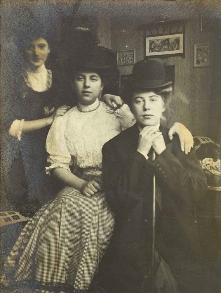 Schwarz-Weiß-Foto von drei jungen Frauen, sie haben sich schräg hintereinander positioniert, die vorderen beiden Damen sitzen, die hintere steht. Im Hintergrund ist eine mit Bildern behängte Wand zu sehen.