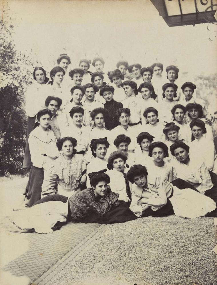 Schwarz-Weiß-Foto einer Gruppe von ca. 40 jungen Frauen im Freien, sie befinden sich neben einem Gebäude, das am rechten Bildrand leicht angeschnitten sichtbar ist. Fast alle tragen Hochsteckfrisuren, weiße Blusen und dunkle Röcke mit weißen Schürzen.