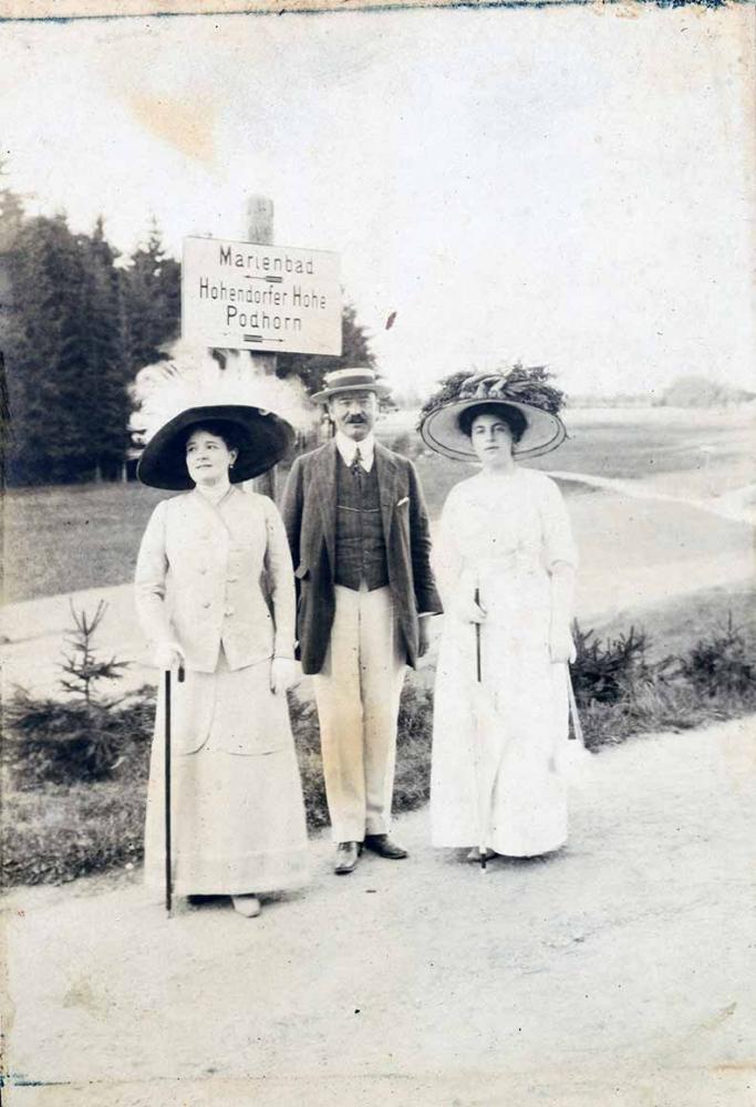 """Das Foto zeigt einen Herrn zwischen zwei Damen auf einem Spaziergang. Sie posieren vor einem Wegweiser, der für """"Marienbad"""" nach links und für  """"Hohendorfer Höhe"""" und """"Podhorn"""" nach rechts weist."""