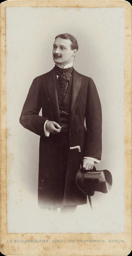 Schwarz-Weiß-Porträtfoto eines stehenden jungen Mannes. Der Körper ist frontal, der Kopf nach links gedreht im Dreiviertelprofil zu sehen. Er trägt einen Schnurrbart und einen Gehrock, in der Hand hält er einen Zylinder und Gehstock mit Fritzgriff.