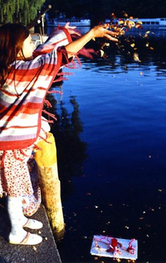 Ein Mädchen wirft Blüten in den Landwehrkanal, wo schon ein selbstgebasteltes Schiffchen schwimmt