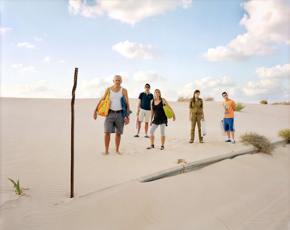 A family of five stands in the sand on a dune with beach bags and folding chairs, their daughter in army clothing