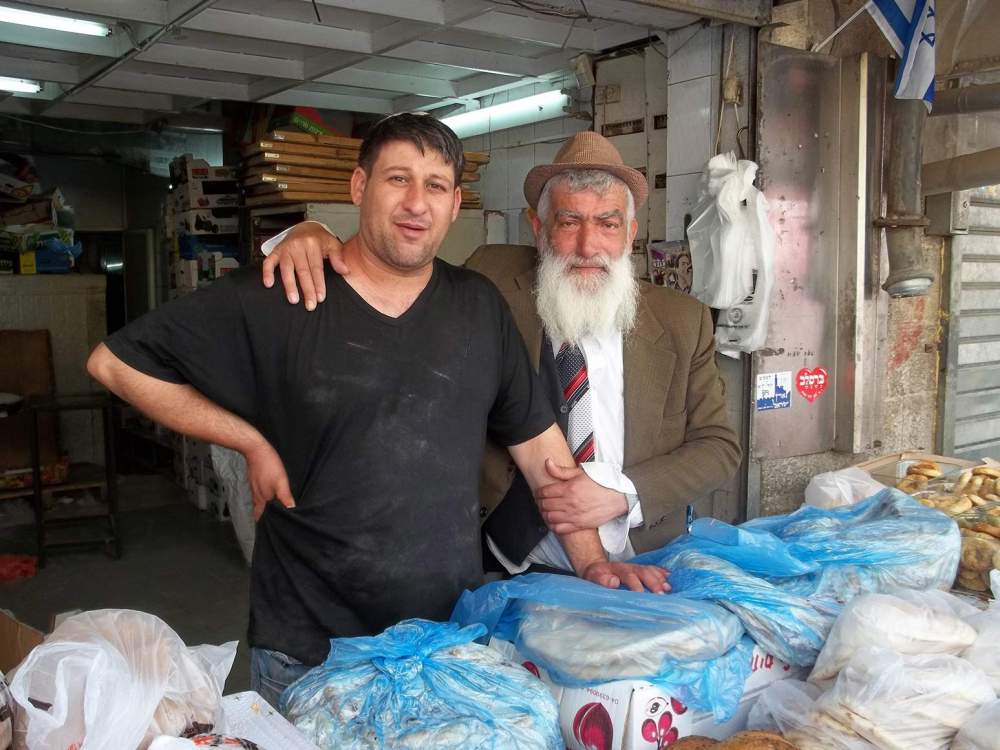 Ein älterer Mann legt den Arm um einen jüngeren Mann, sie posieren hinter einem Stand mit Fladenbroten