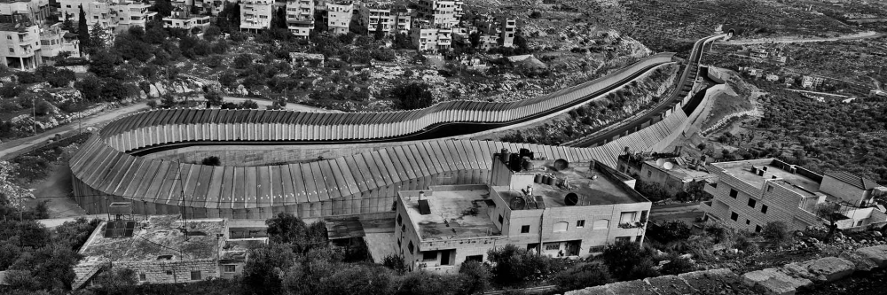 Black-and-white photo of a motorway, shielded from the surrounding houses by high walls