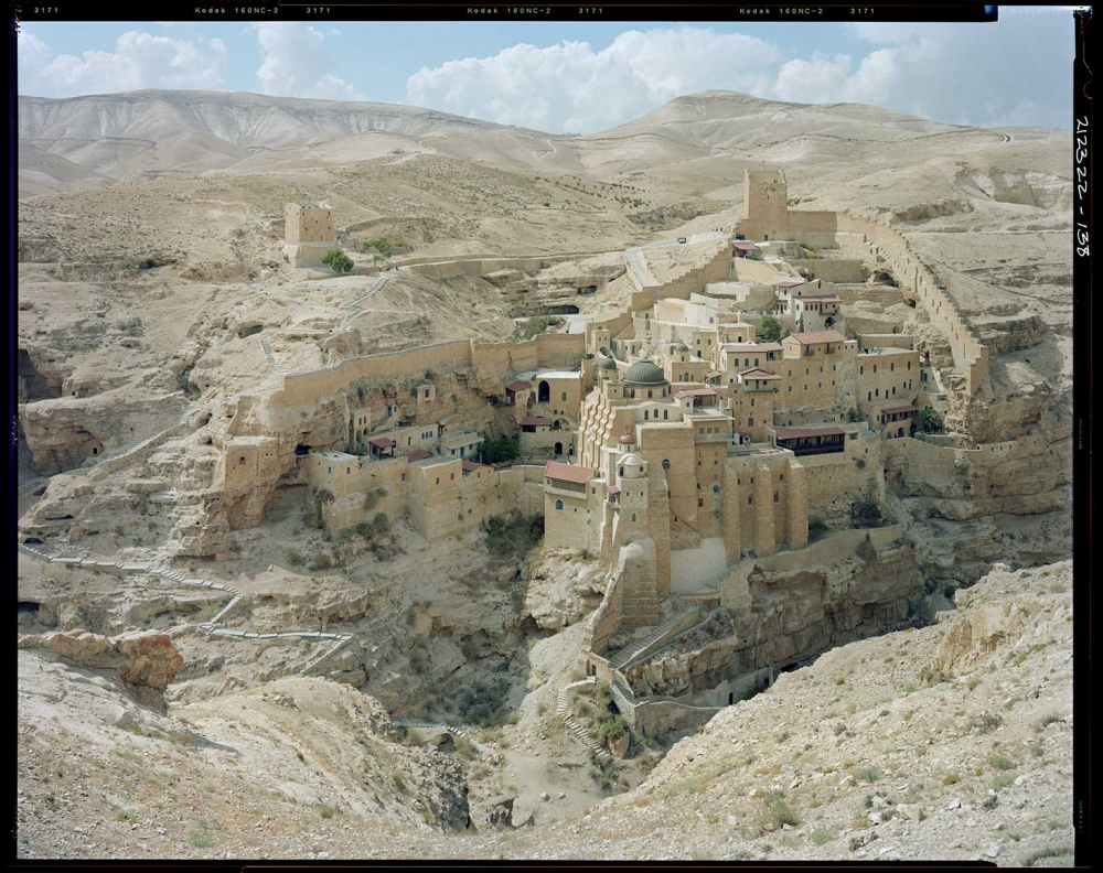 Foto einer am Hang gebauten steinernen Stadt in einer Wüstenlandschaft