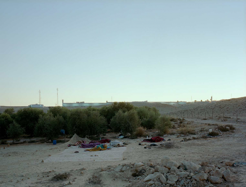 Outdoor sleeping camp on sandy and stony ground, behind it a few trees, on the horizon buildings in the morning light