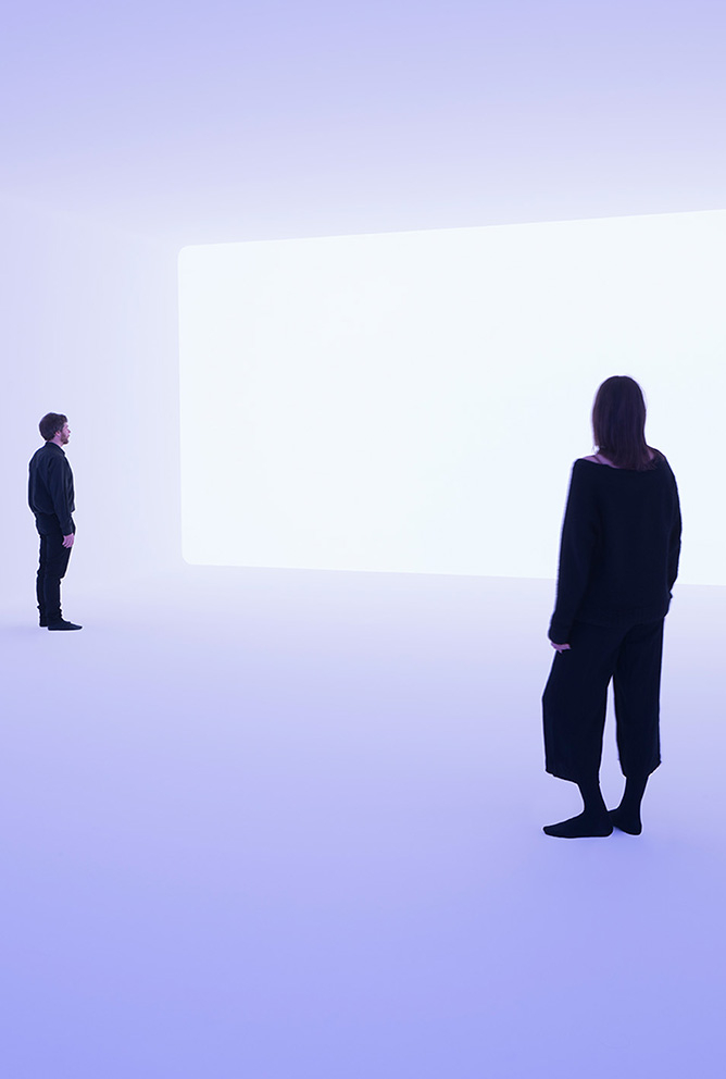 A man and a woman stand in a light blue room and look towards a white rectangle on the wall