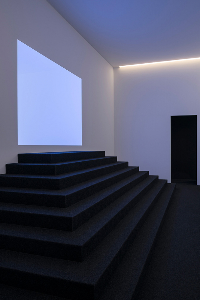 A dark staircase leads towards an empty wall that features a rectangular light field