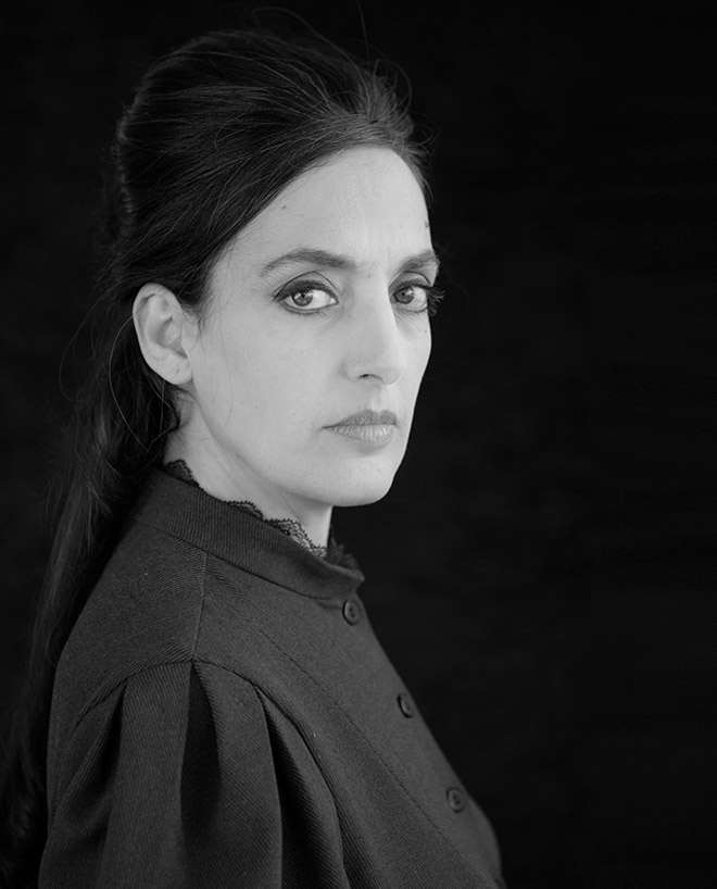 Portrait of Victoria Hanna in high-necked black clothes, with a strict but attentive look.