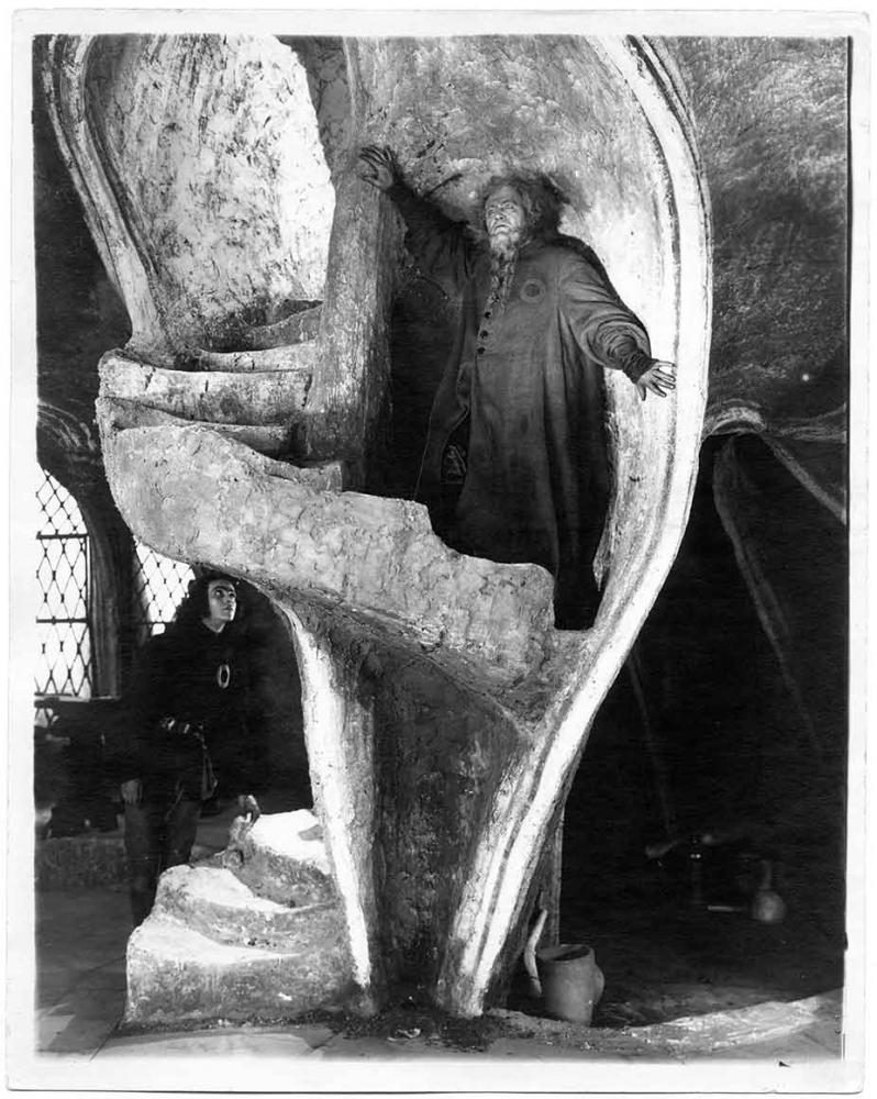 Ein Mann mit Bart und Mantel auf einer Wendeltreppe