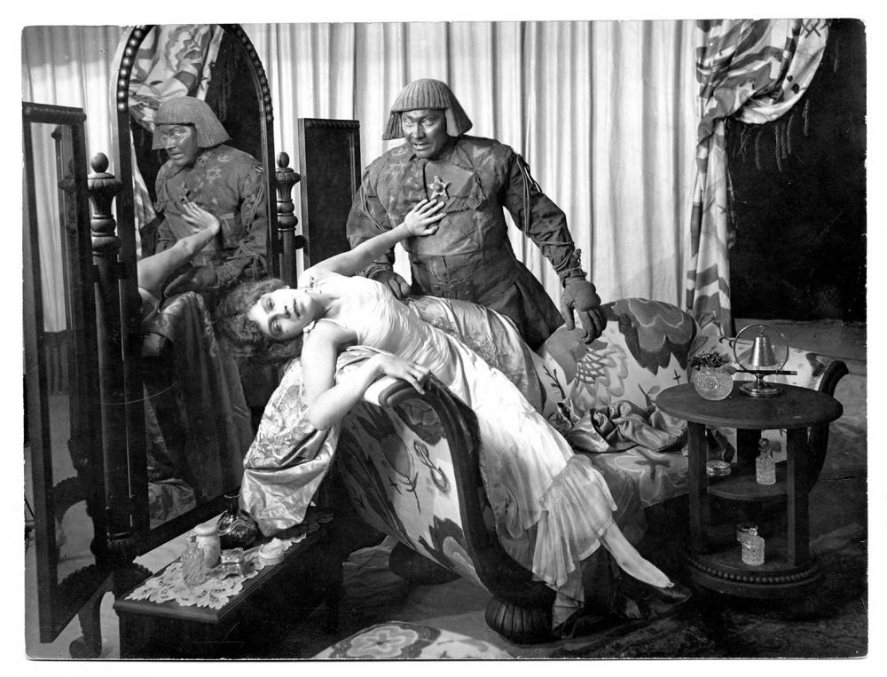 Szene, in der sich der Golem über eine halb ohnmächtig auf dem Sofa liegende Taenzerin beugt