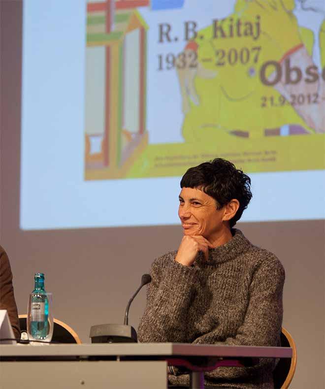 Junge Frau mit schwarzem Kurzhaarschnitt auf einem Podium