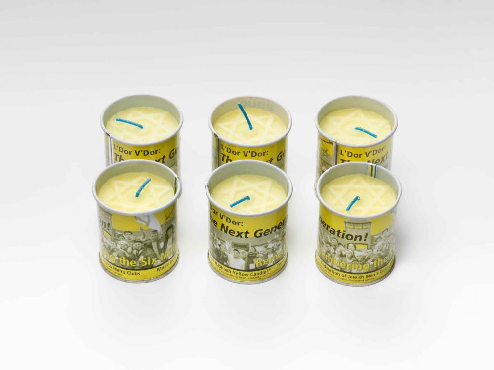 Sechs gelbe Kerzen in bedruckten gelben Dosen. Auf der Oberfläche jeder Kerze ist ein hellgelber Davidstern zu erkennen.