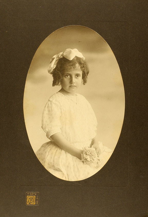 Studio photo of a girl in a white dress, with a bow in her hair and a fabric flower in her hand