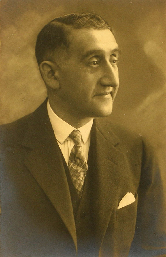 Portrait photo of a man with suit and tie in half profile
