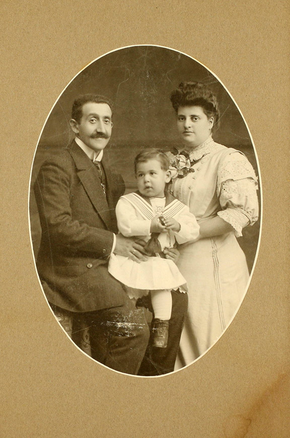 Oval studio photo of a couple with a small child on the father's lap