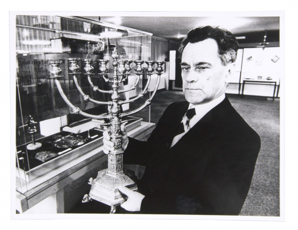 Black and white photo of man in suit with big hanukkah menorah in hand