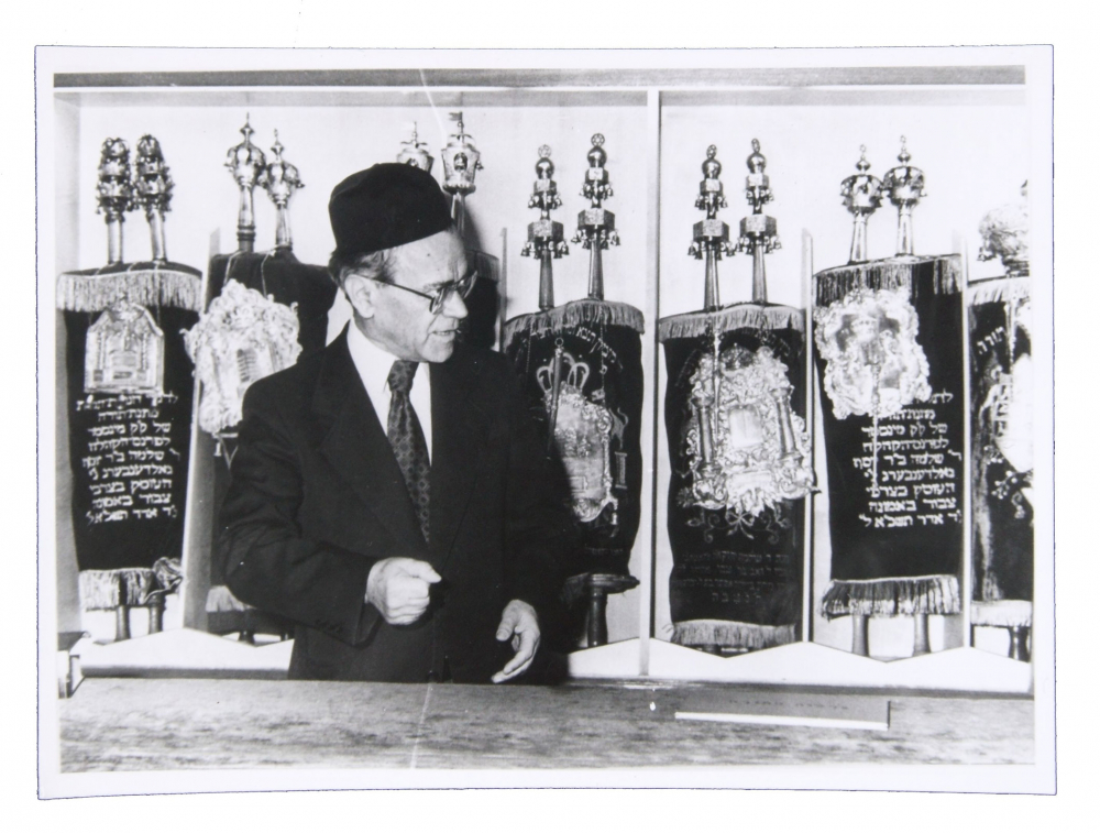 Black and white photo of man in suit in front of nine Torah scrolls