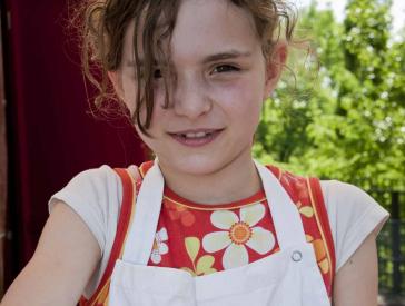 Mädchen mit Küchenschürze knetet Teig