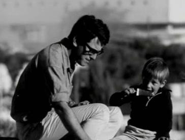 Filmszene: Ein Mann und ein Junge sitzen nebeneinander. Der Mann sieht nach unten, der Junge isst ein Eis.